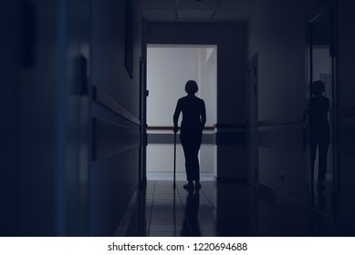 Woman is using crutch for moving in hospital. She is crossing dark hallway with focus on back. Copy space in left side