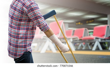 woman using crutches for patient broken leg isolated on blurred background row of seats in departure area in airport terminal.