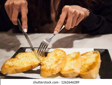 Woman using cutlery cut freshly Baked Tasty Homemade Garlic Bread servings. Food ingredient, bakery, pastry, snack, appetizer, starter, hors d'oeuvre, entree, course menu, hotel and restaurant concept