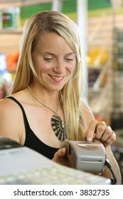 Woman using debit terminal to make a retail purchase