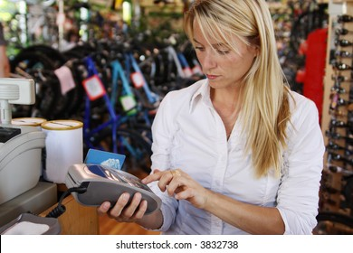 Woman using debit terminal in retail store to make a purchase.