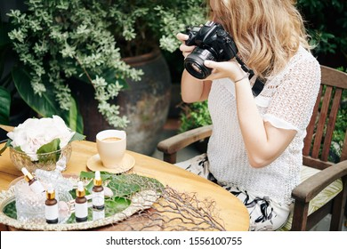 Woman using digital camera to take photos of organic cosmetics for social media and online store