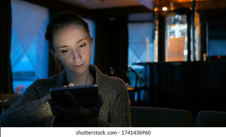 Woman using digital tablet computer device in cafe of cruise ship. Evening time, lowlight. Technology and entertainment concept