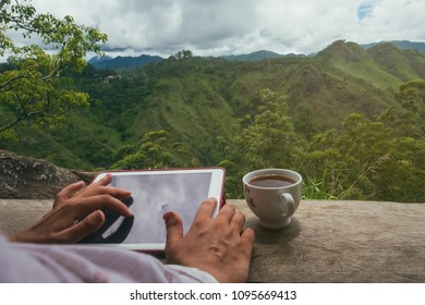 Woman using digital tablet PC sitting outdoor and drinking tea. Concept of asian travel