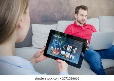 Woman using digital tablet for watching movie on VOD service. Video On Demand television internet stream multimedia concept