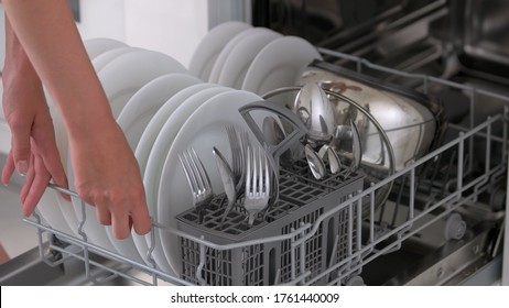 Woman using dish washing machine at kitchen. Open built-in dishwasher machine with clean dishes close up. Household chores concept.