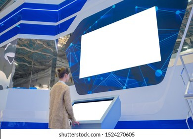 Woman using electronic kiosk and looking at white blank large interactive wall display in dark room of modern technology exhibition. Mock up, futuristic, template, education and technology concept