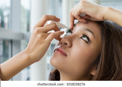 woman using eye drop, woman dropping eye lubricant to treat dry eye or allergy; sick asian girl treating eyeball irritation or inflammation; sick woman suffering from irritated eye, optical symptoms