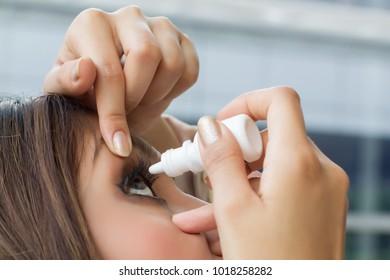 woman using eye drop, eye lubricant to treat dry eye or allergy