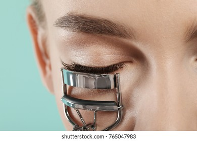 Woman using eyelash curler, closeup