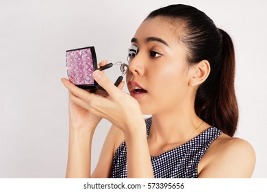 Woman using an Eyelash Curler on White Background, Makeup Concept