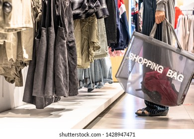 Woman is using a fabric cotton reuse shopping bag while selecting clothes in a shop. Zero waste shopping concept.