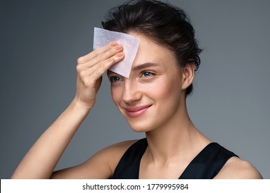 Woman using facial oil blotting paper. Photo of woman with perfect makeup on gray background. Beauty concept