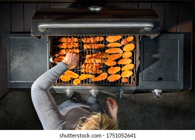 Woman using a gas grill in an outdoor kitchen. Shish kebab on skewers and sweet potato.