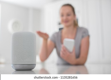 Woman Using Gesture Control With Digital Assistant At Home In Kitchen