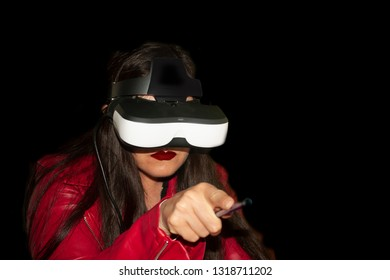 Woman using glasses for alternating reality simulation is a young woman with long brown hair with red jacket living augmented reality experience looking curiously at the environment