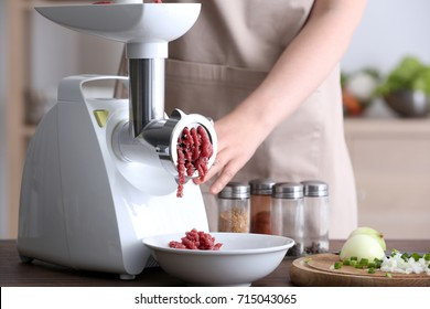 Woman using grinder for preparation of minced meat in kitchen