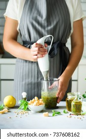 Woman using hand blender to make pesto. White kitchen interior design. Copy space. Vegetarian, clean eating lifestyle concept