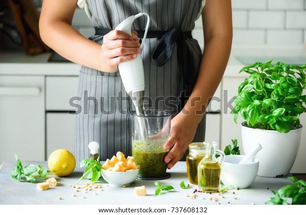 ペストを作るのに手ミキサーを使う女性。白いキッチンの内装デザイン。スペースをコピーします。ベジタリアン、清潔な食生活のコンセプト