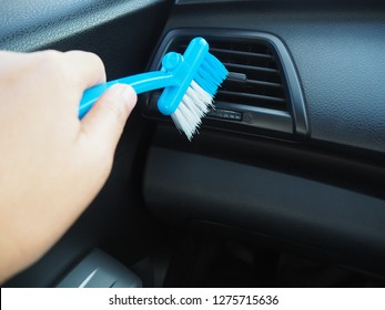 Woman using hand hold a car cleaning blue brush for airconditioner cleaner on grid panel console, copy space.