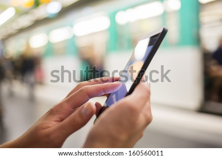 Woman using her cell phone on subway platform, message sms e-mail