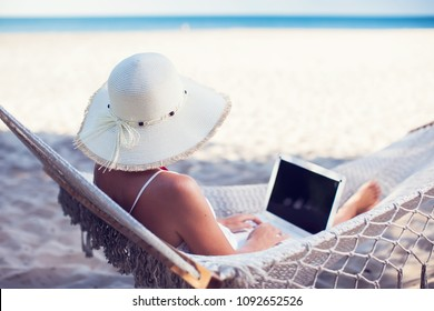 Woman using her laptop in hammock on the beach