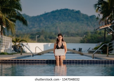 Woman using her laptop on the pool edge on a sunny day. Freelance work in tropical country