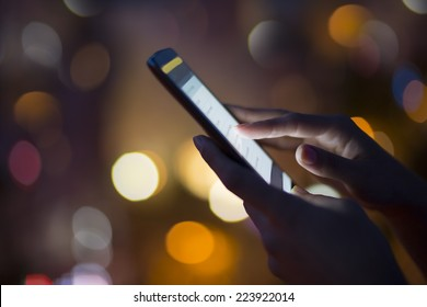 Woman using her mobile phone, city skyline night light  background