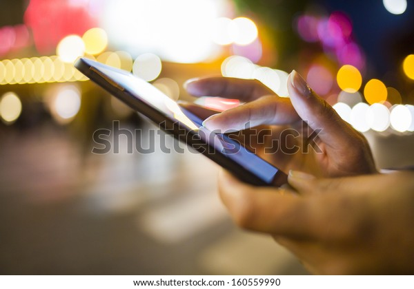 Woman using her Mobile Phone in the street, night light Background