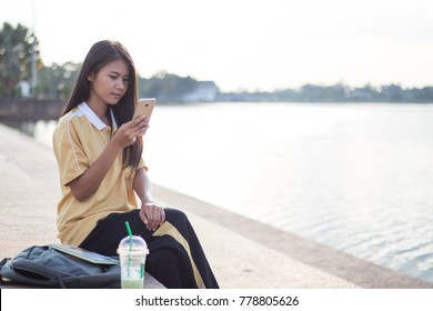 Woman using her smart phone at the park.
