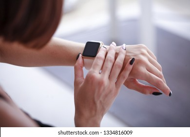 Woman using her smartwatch at home in the living room