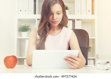 Woman using her tablet computer at work in sunlit office. Big red apple and glass of water on table. Bookcase with binders at background.  Toned image