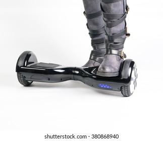 Woman using hoverboard, a self-balancing two-wheeled board.