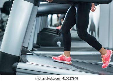 Woman using incline threadmill in modern gym. Incline threadmills are used to simulate uphill walking or running and deliver additional workout benefits to users.