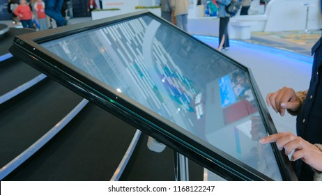 Woman using interactive touchscreen display at urban exhibition - scrolling and touching. Education and technology concept