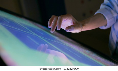 Woman using interactive touchscreen display at modern museum. Education and technology concept