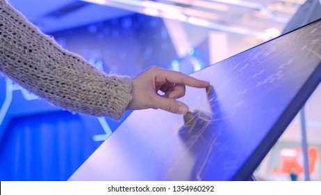 Woman using interactive touchscreen display with unrecognizable virtual map at modern technology show with futuristic interior