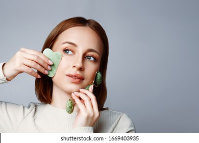 Woman using jade facial roller and gua sha stone for skin care, morning daily beauty treatment on grey background. Girl using natural massager closeup studio portrait. Face massage and beauty trends.