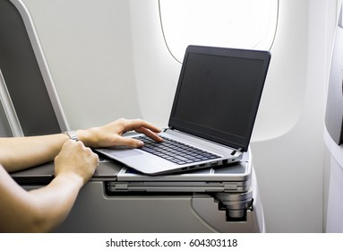 Woman using laptop in airplane