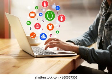 Woman using laptop for browsing internet store at table, closeup. Online shopping concept