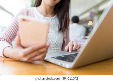 Woman using laptop computer and cellphone