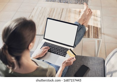 Woman using laptop computer and credit card at home. Businesswoman, entrepreneur working. Blank, white, empty, copyspace display screen. Online shopping, home work, ecommerce, internet banking concept