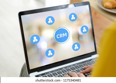 Woman using laptop computer with CRM, Customer Relationship Management, icon on screen background, success in business concept