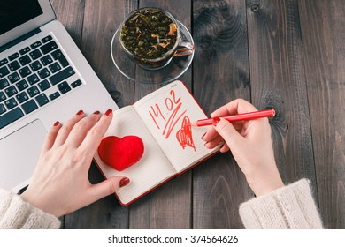 woman using laptop computer and drawing red heart