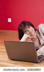 Woman using the laptop computer at her house floor, next to a red wall (selective focus)