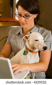 Woman using laptop computer with pet dog in lap.