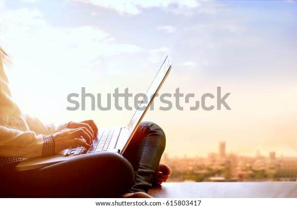 Mujer usando ordenador portátil y sentada en la vista de un rascacielos con paisaje urbano.
