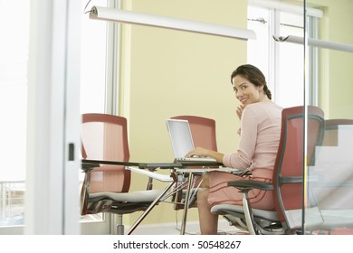 Woman using laptop in conference room, portrait