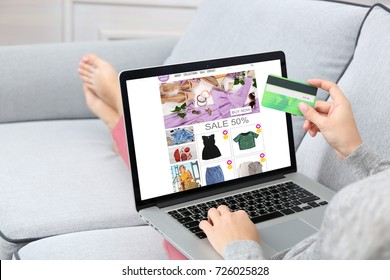 Woman using laptop and credit card for internet online shopping at home