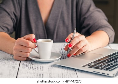 Woman using laptop with a cup of coffee